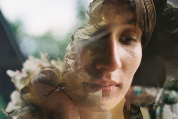 Double exposure of thoughtful young woman and flowers