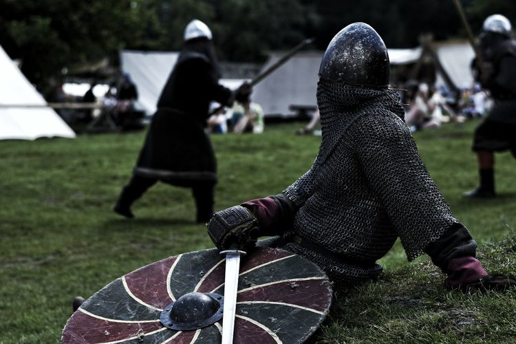 Warrior with sword and shield sitting on field