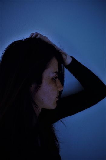 Side view of woman with hand in hair against wall