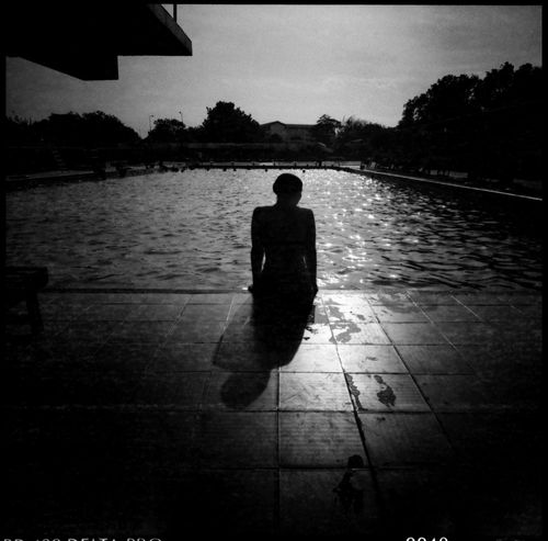 Romance at the Pool Abandoned Places Analogue Photography Architecture Football Ghana Swimming Travel WestAfrica Abandoned Stadium Adventure Black And White Black And White Photography Football Stadium Girl Silhouette Grain Outdoors Pool Pool Shadow Poolside Rough Edges Shadow Swimming Pool Swimming Time Tiles Water
