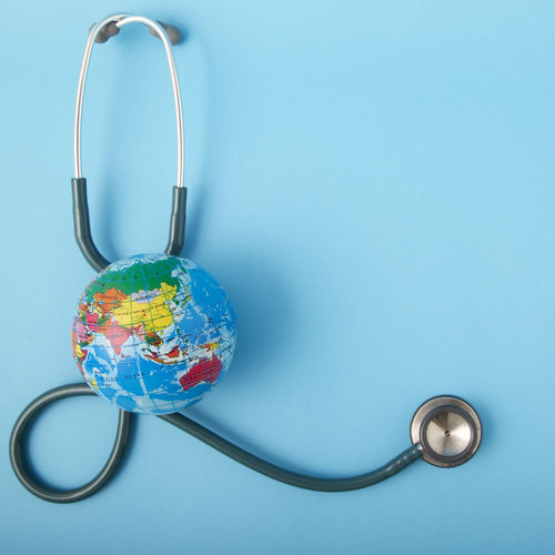 Close-up of stethoscope with globe over blue background