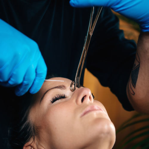 Cropped hands piercing woman eyebrow
