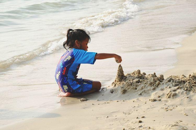 Girl making sandcastle on shore at beach