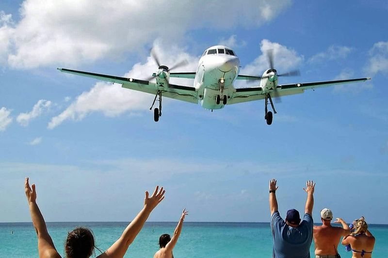 Rear view of people with arms raised looking at airplane flying over sea