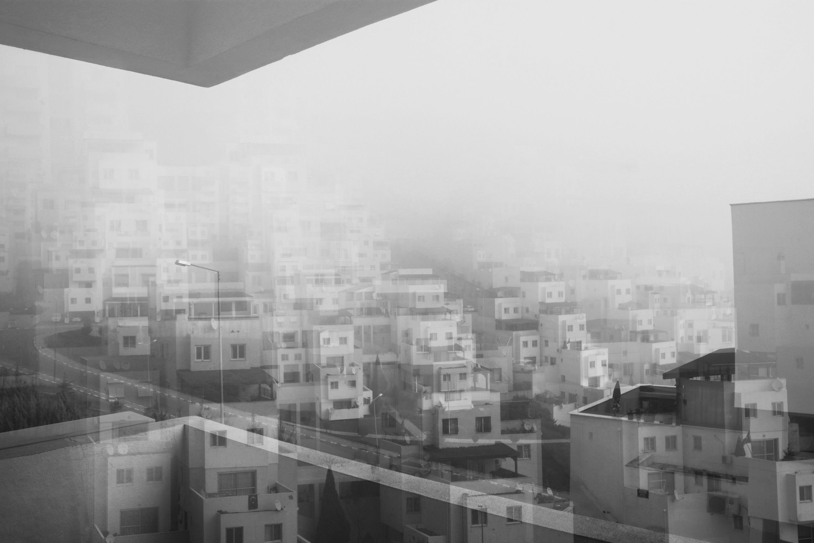 architecture, building exterior, built structure, city, clear sky, cityscape, residential building, residential structure, residential district, copy space, building, high angle view, day, sky, foggy, city life, window, crowded, no people