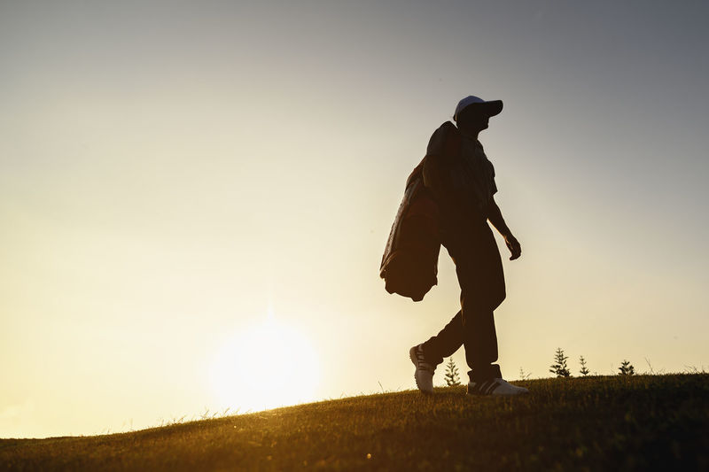 Low angle view of silhouette man walking on land against clear sky during sunset