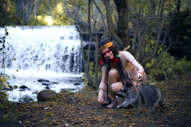 Young Woman In Traditional Clothing With Raccoon In Forest