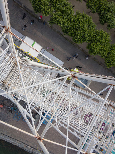 View to the hub of a Ferris wheel from above High Angle View Day Plant No People Architecture Built Structure Transportation City Nature Outdoors Metal Mode Of Transportation Road Tree Railing Street Land Vehicle Sunlight Building Exterior Bridge Ferris Wheel Hub