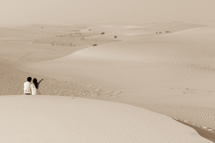 Rear View Of Couple Sitting On Sand At Desert During Sunny Day
