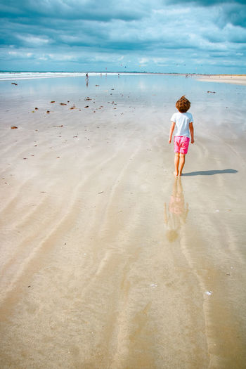 Rear view of girl wading in sea against sky