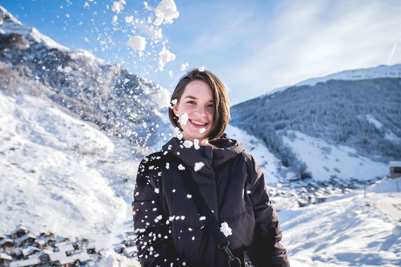Portrait of smiling young woman on snowcapped mountains during winter