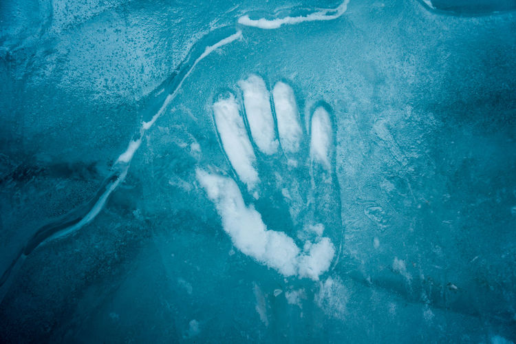 Hand print on the blue ice