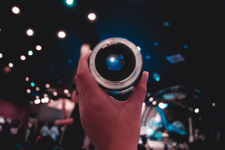 Close-up of hand holding lens at night