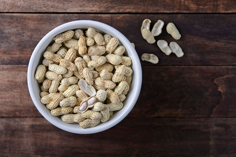 Close up peanut on wooden table Groundnut Diet Bowl Close-up Crop Plants Food Food And Drink Freshness Goober Healthy Eating High Oil Hypogaea Ingredient Peanut Table Vitamin White Wood - Material