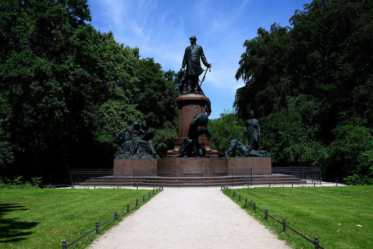 Statue in park against sky