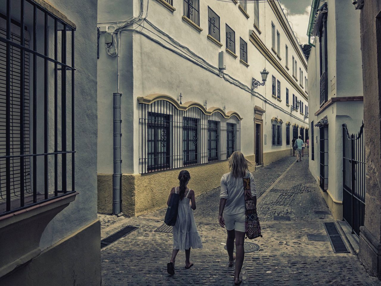 walking, two people, rear view, real people, building exterior, architecture, built structure, full length, street, togetherness, women, lifestyles, the way forward, day, leisure activity, girls, city, outdoors, pedestrian, warm clothing, adult, people