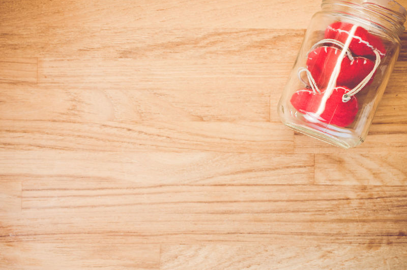 High angle view of heart shape in jar on hardwood floor