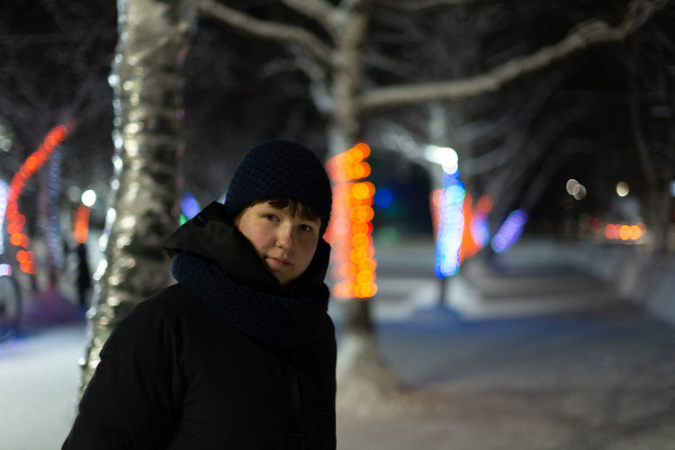 Portrait of man standing in illuminated city during winter