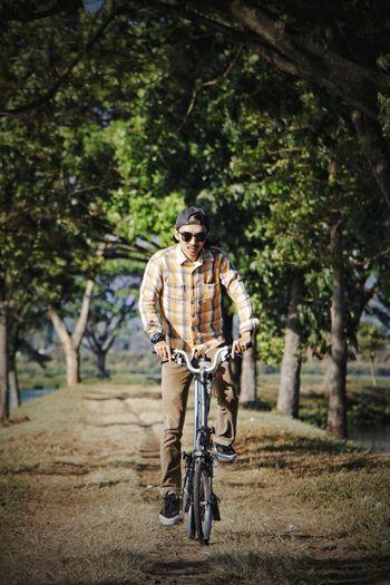 Portrait of man riding brompton folding bicycle on tree