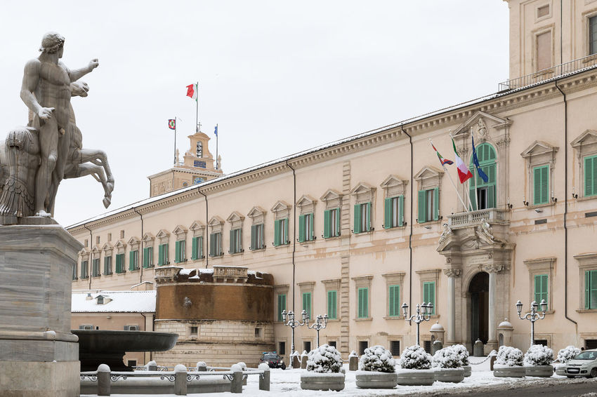 Rome, Italy - February 26, 2018: An exceptional weather event causes a cold and cold air across Europe, including Italy. Snow comes in the capital, covering streets and monuments of a white white coat. In the photo, Piazza del Quirinale, home of the President of the Republic. Government Institutional Buildings President Quirinale Architectural Column Architecture Building Exterior Built Structure City Day Flag Governmental Headquarters Human Representation Italian Flag No People Outdoors Palace Patriotism Quirinal Republic Residence Sculpture Sky Snow Snowing Statue Symbolic  Travel Destinations