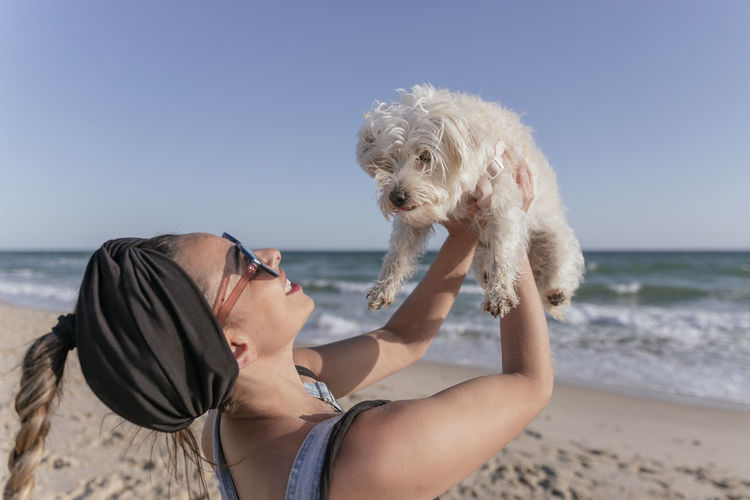 Rear view of woman with dog on beach against sky
