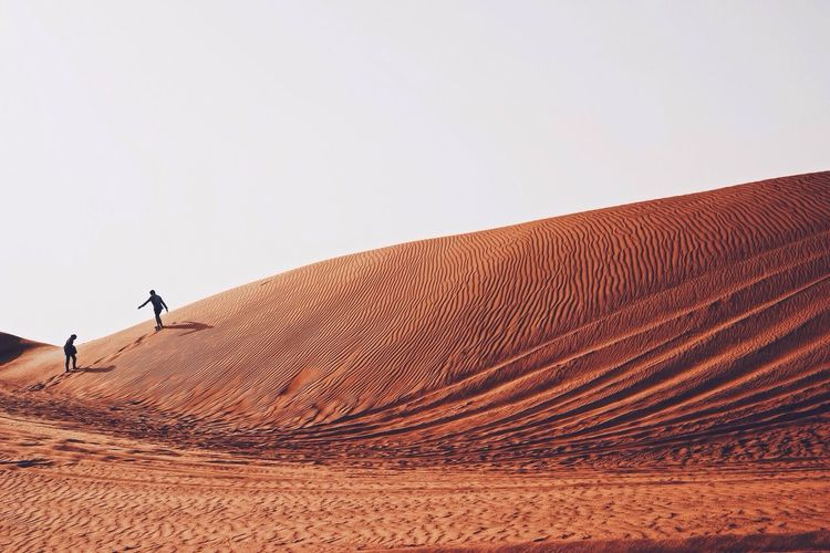People on sand dune in dessert against clear sky