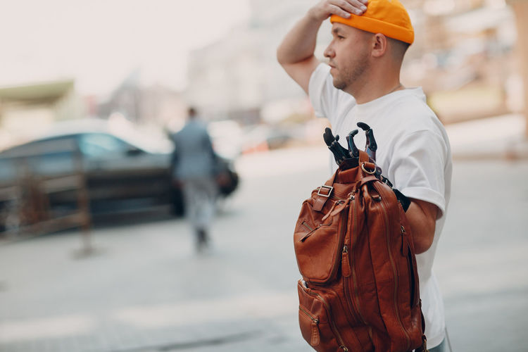 Side view of man holding umbrella standing on street