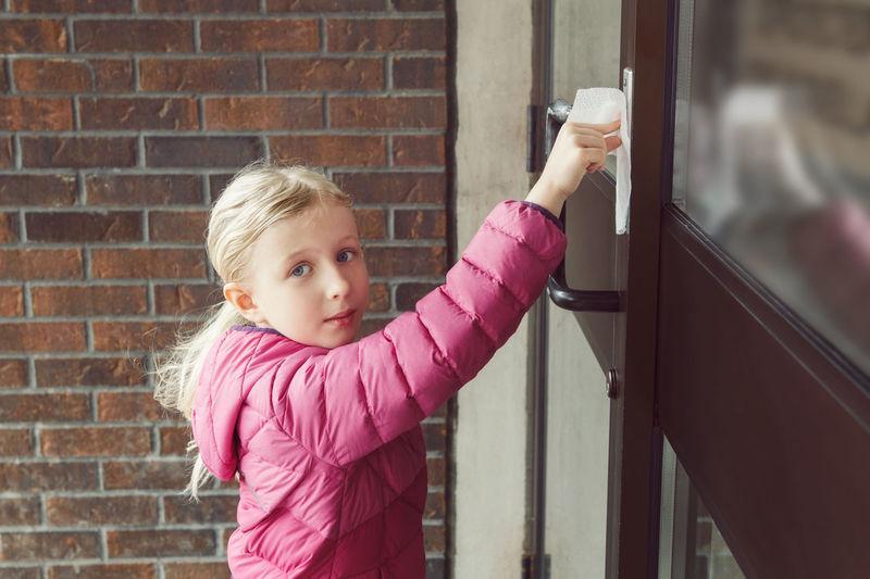 Girl with napkin pressing doorbell