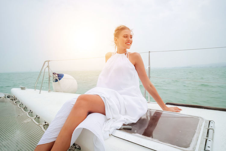 Woman sitting on boat against sea against sky
