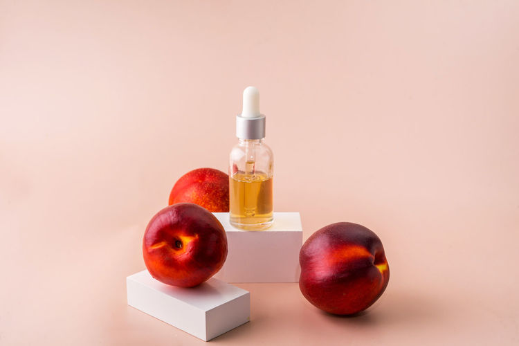 Close-up of apples on table against orange background