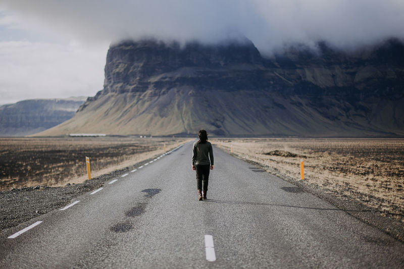 Rear view of woman walking on road against mountain