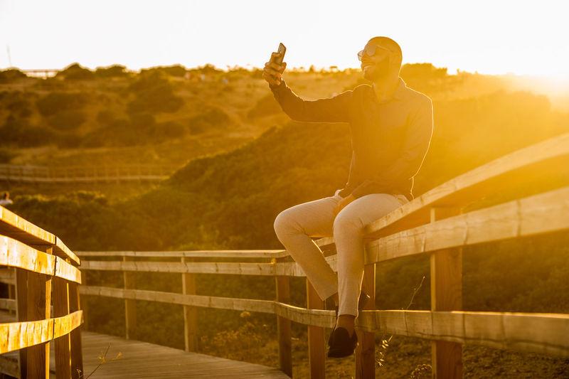 Man sitting on railing against sky