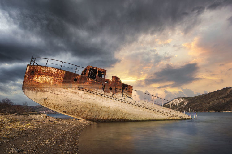 Abandoned ship on beach against sky during sunset