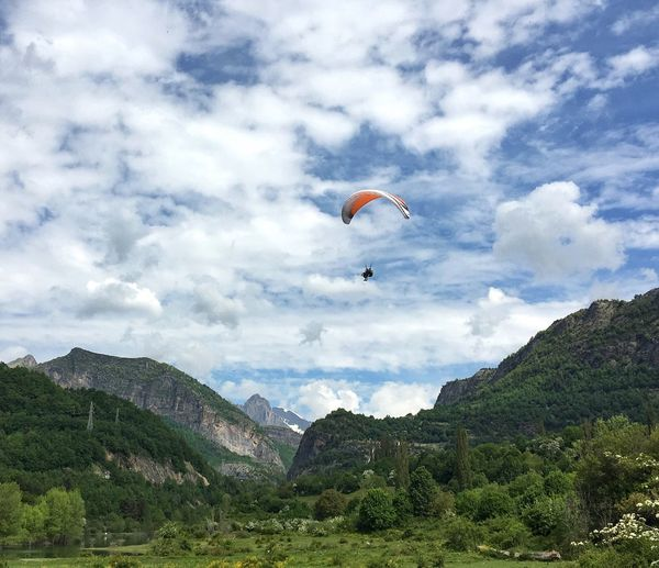 Low Angle View Of Person Paragliding Over Mountains Against Cloudy Sky