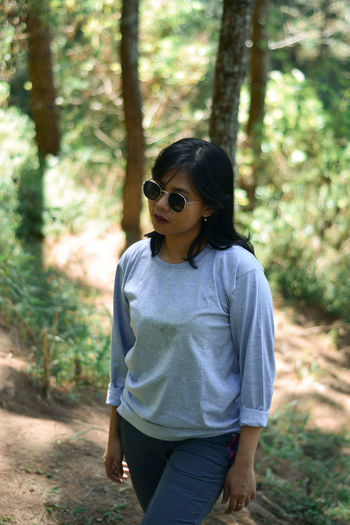 Low section of person wearing sunglasses standing in forest