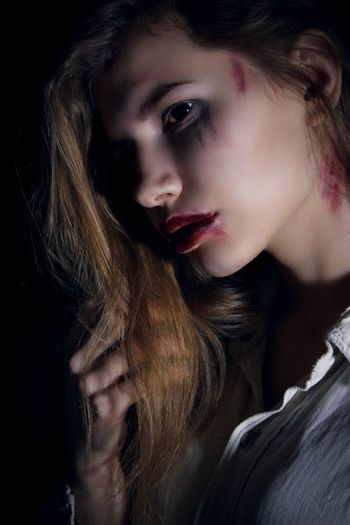 Close-Up Of Thoughtful Woman With Wounds Against Black Background