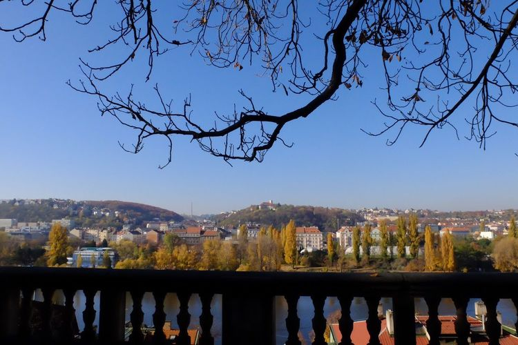 Scenic view of river and buildings against clear blue sky