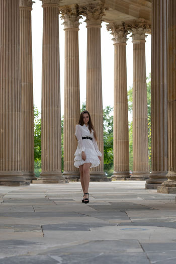 Full length of young woman standing against columns