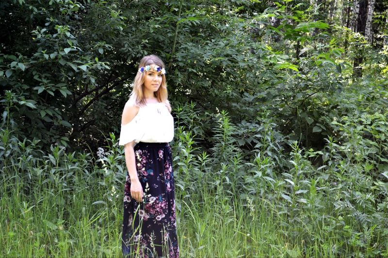 Portrait of beautiful woman standing against trees on field