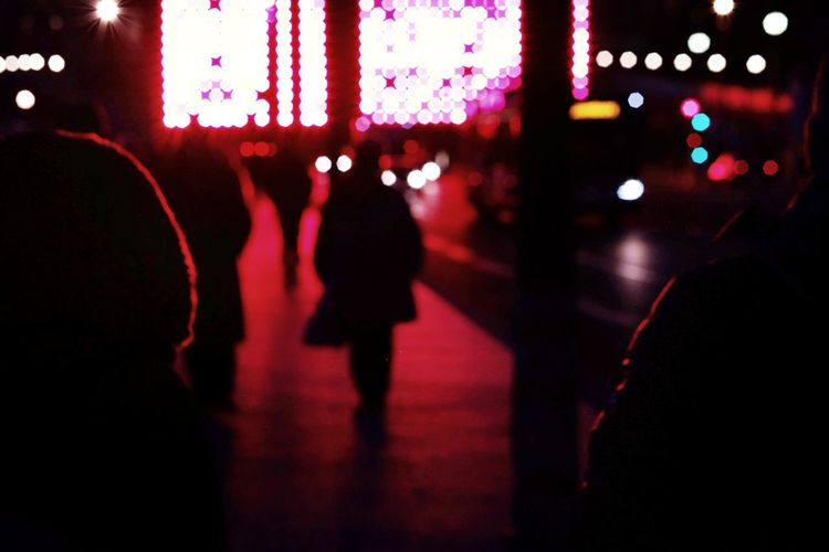 Silhouette people in illuminated city at night