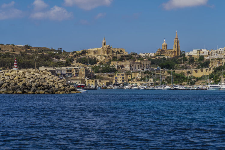 Gozo Island, Malta Gozo port landscape. Moored boats at port with background view of city buildings, Lourdes Chapel and Ghajnsielem Parish Church on the hill. Ghajnsielem Parish Church Gozo Island Malta Gozo Church Gozo Moored Boats Gozo Port Il-Kapppella Ta Lourdes Lourdes Chapel Malta Malta Malta Architecture Maltese Religion Sightseeing Summer Vacation Unesco Malta Gozo Gozo Island Buildings Malta Landscape Maltaphotography Maltese Republic Of Malta Residential District Tourism Travel Travel Destinations Water Waterfront