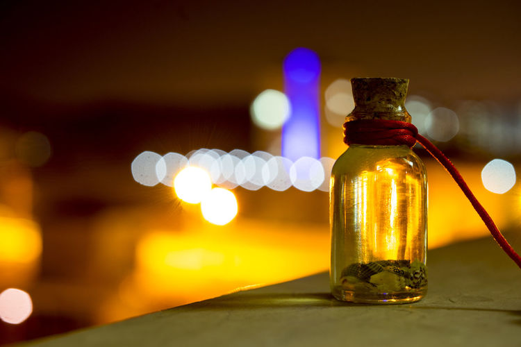 Glass bottle on table at night