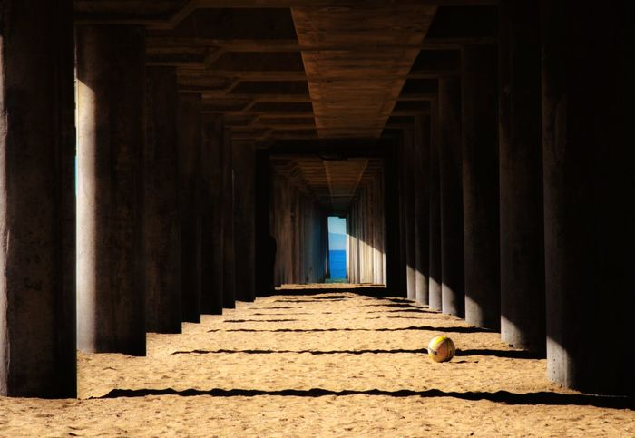 Under The Pier IShootFromMyWheelchair Pier Outdoor Photography Beach Beach Photography Photo Of The Day Ball Volleyball Under The Pier Isolation Ocean Light At The End Landscape Outdoors EyeEm Eyeem Market EyeEm Best Shots Shadow And Light Sand Perspective Surf City USA Huntington Beach Pier Sports Sports Photography Beach Sports