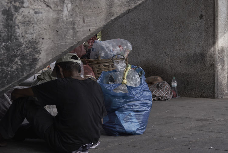 Rear view of man sitting by garbage on sidewalk
