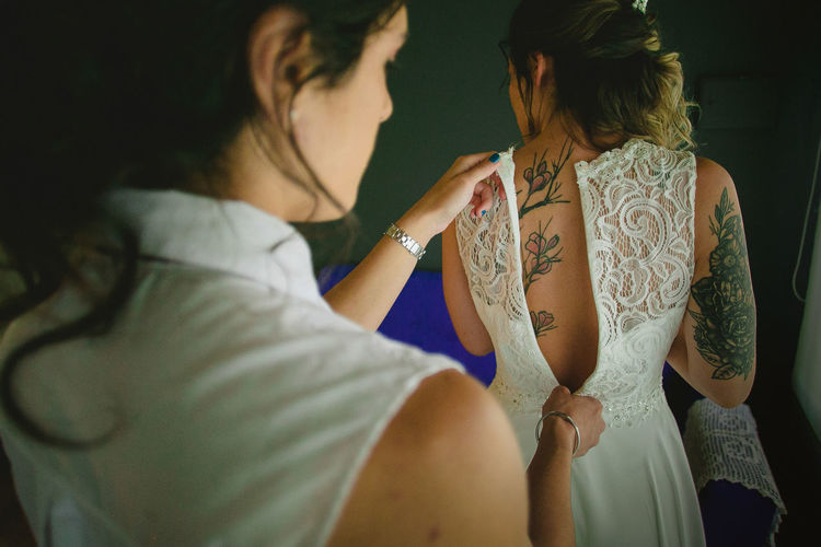 Rear view of woman zipping bride dress