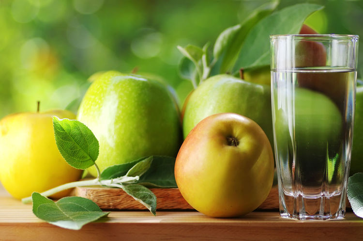 fresh ripe apples and glass of water Apple Apple - Fruit Close-up Drink Drinking Glass Food Food And Drink Freshness Fruit Glass Green Color Healthy Eating Leaf Leaves Table