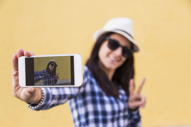 Young woman photographing with mobile phone