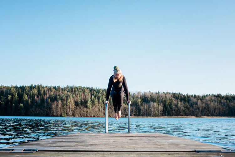Man standing by swimming pool by lake against clear sky