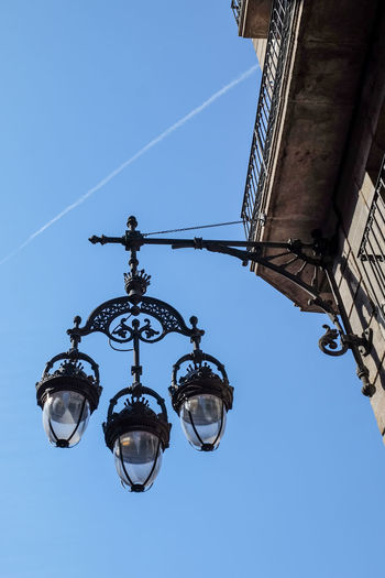 Low Angle View Of Lanterns Mounted On Building Wall Against Blue Sky