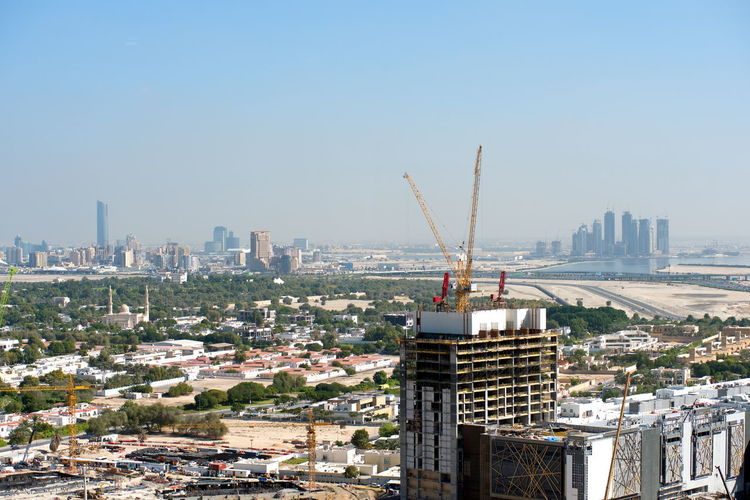 Aerial view of crane and buildings against clear sky